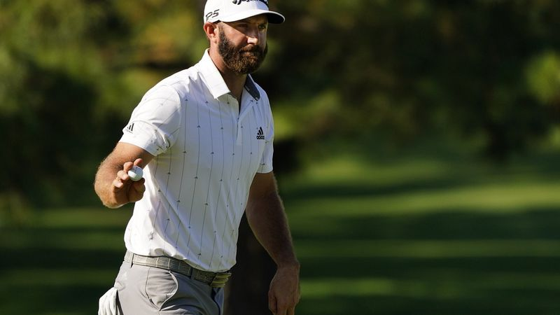 Dustin Johnson waves his ball after a birdie on the seventh hole during the third round of the...