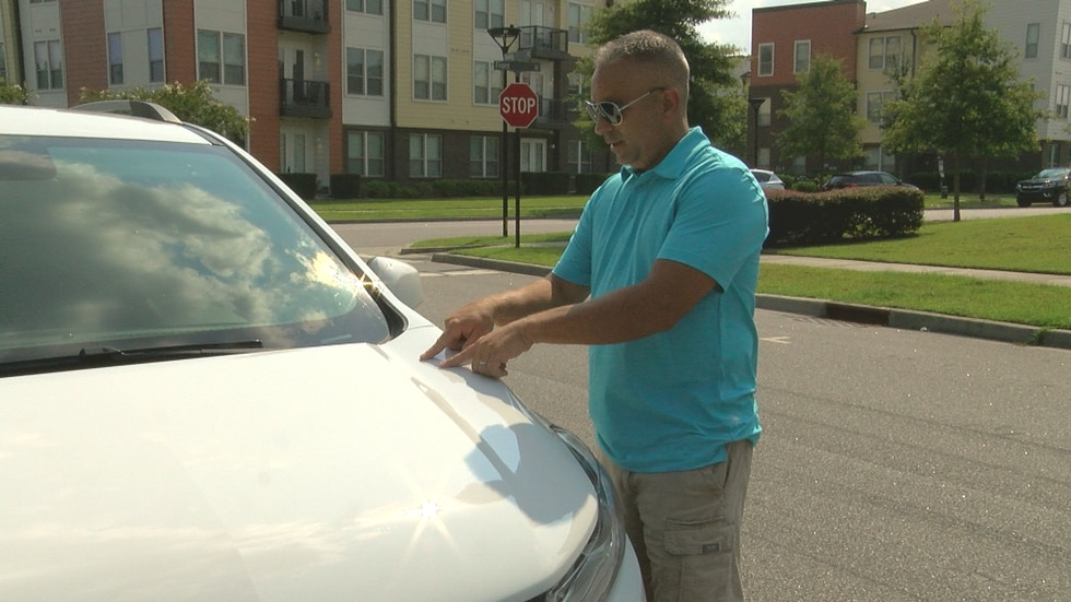 Dwight Kress points to the spot on the hood of his SUV where flying debris in a construction...