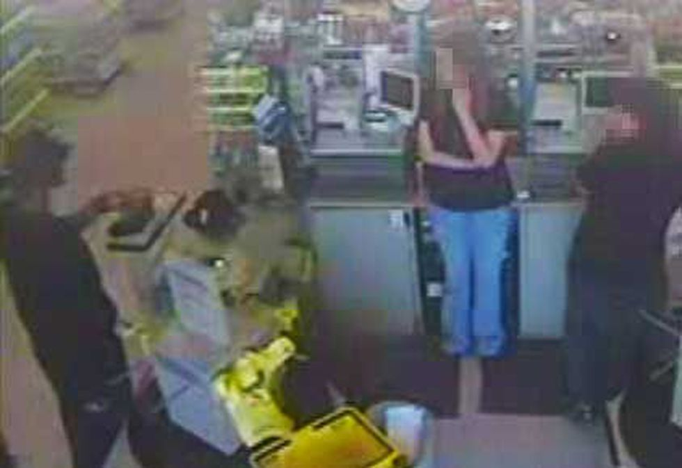 One of the suspects demanding money at the Dollar General.