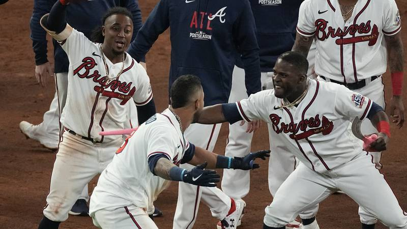 Atlanta Braves' Eddie Rosario is congratulated by teammates after hitting the game winning RBI...