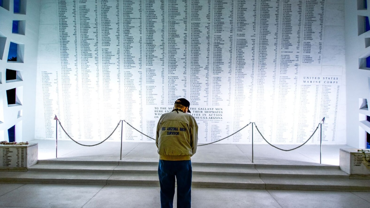 USS Arizona survivor Donald Stratton bows his head before the remembrance wall that lists the...
