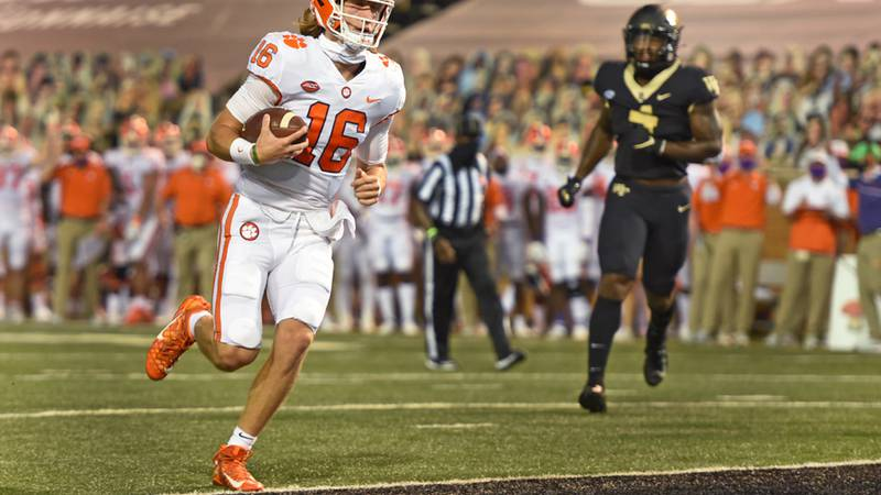 Clemson quarterback Trevor Lawrence is untouched as he scores in the first half of an NCAA...
