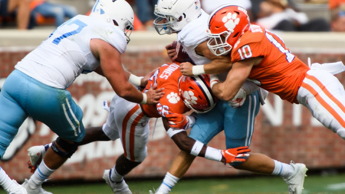 The Citadel freshman Cooper Wallace (27) is tackled by Clemson linebacker Baylon Spector (10)...