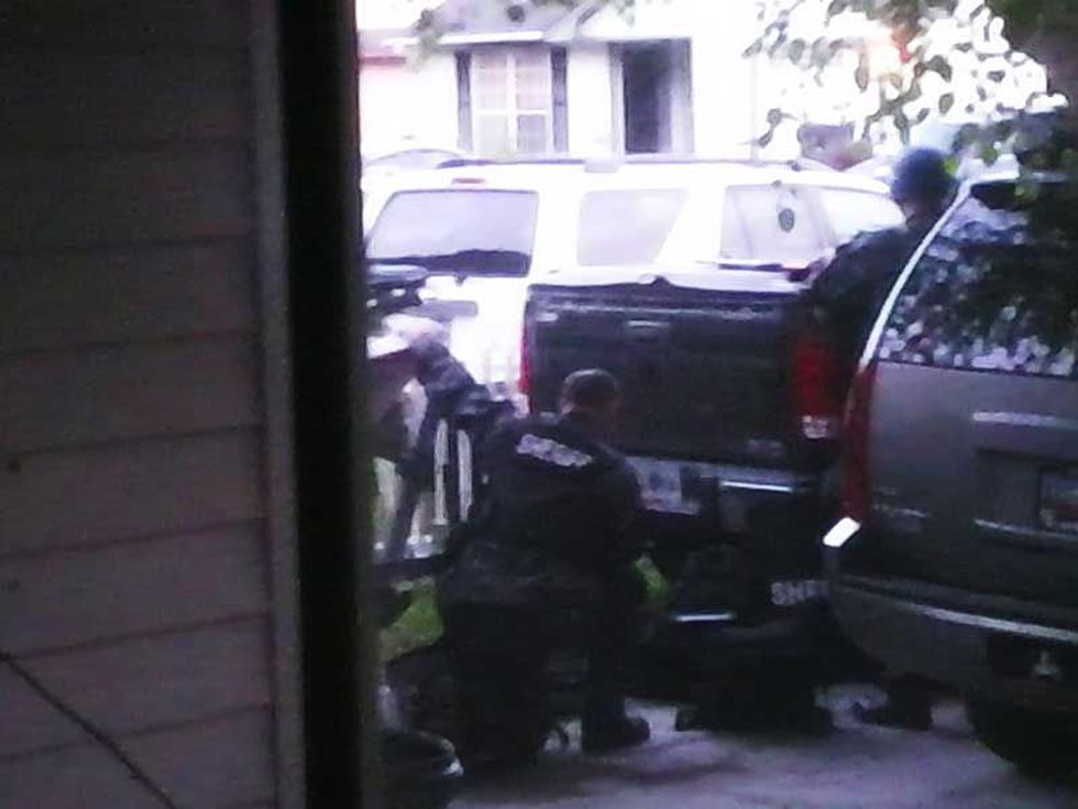 Viewer picture of law enforcement taking cover behind neighborhood cars.