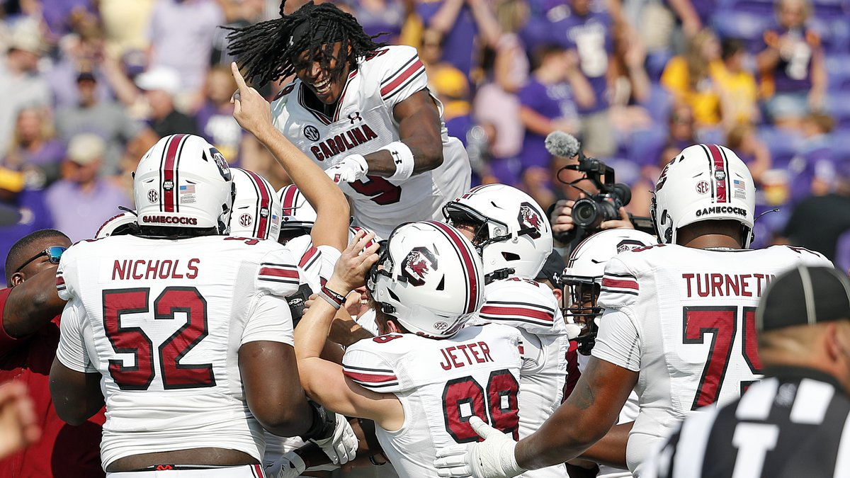 South Carolina's Cam Smith (9) jumps on top of teammates celebrating their win over East...