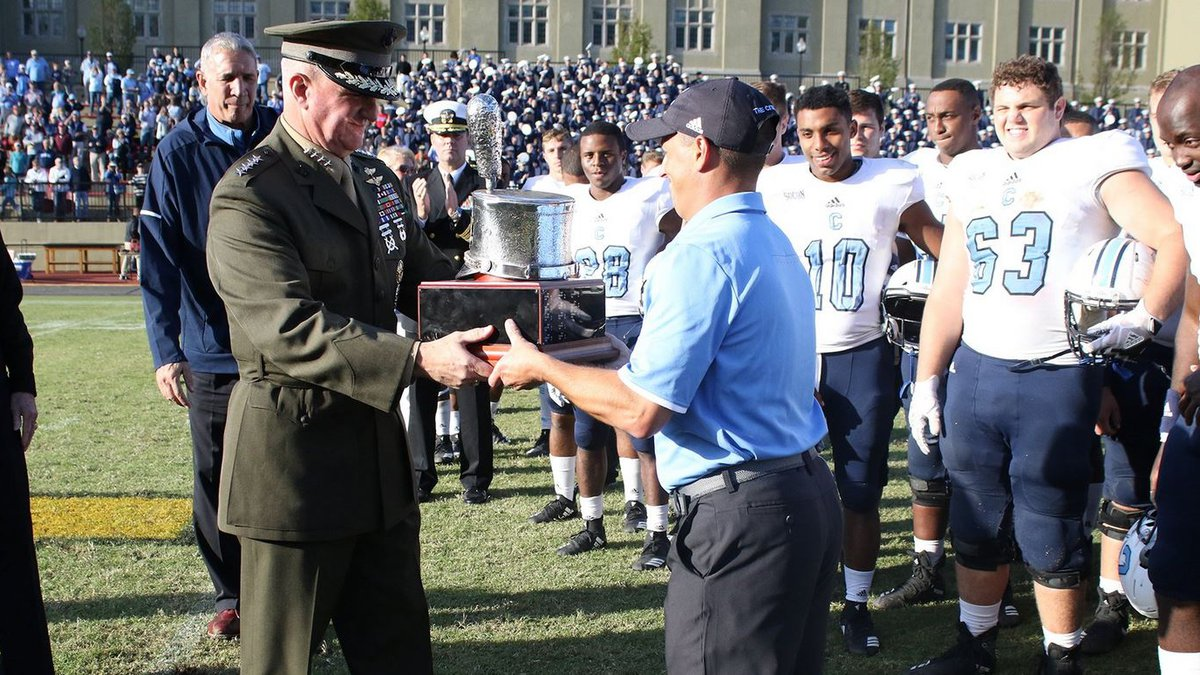 The Citadel head coach Brent Thompson (right) accepts the Silver Shako award after the Bulldogs...