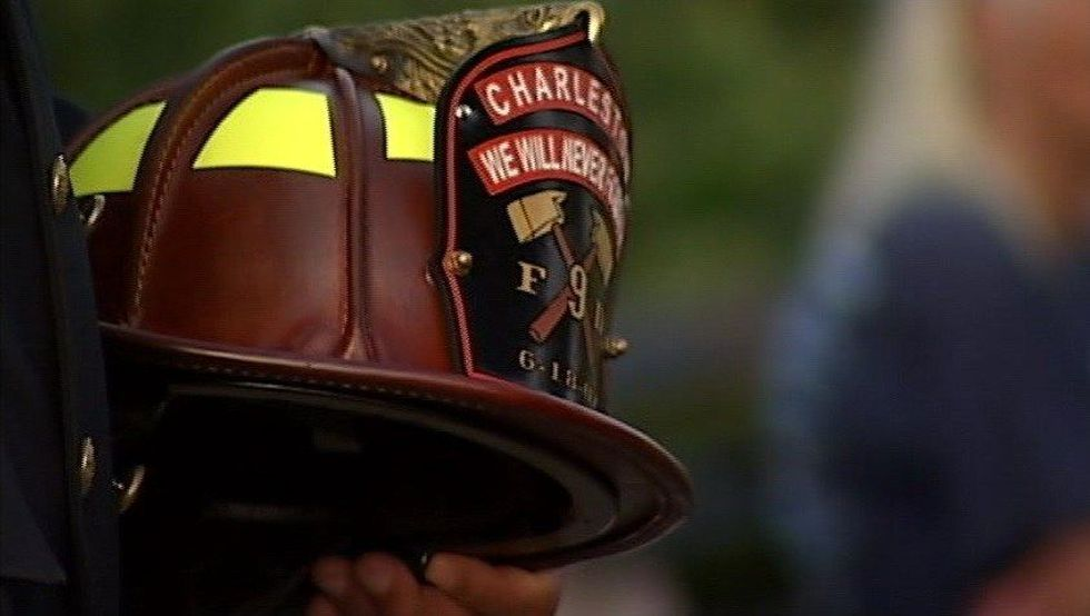 A firefighter holds a helmet in tribute to the Charleston 9 at a memorial service. (Source:...