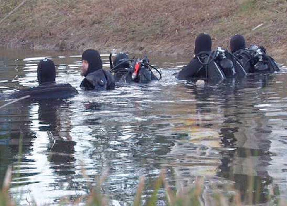 Divers search a pond in the Rivertowne subdivision Thursday.