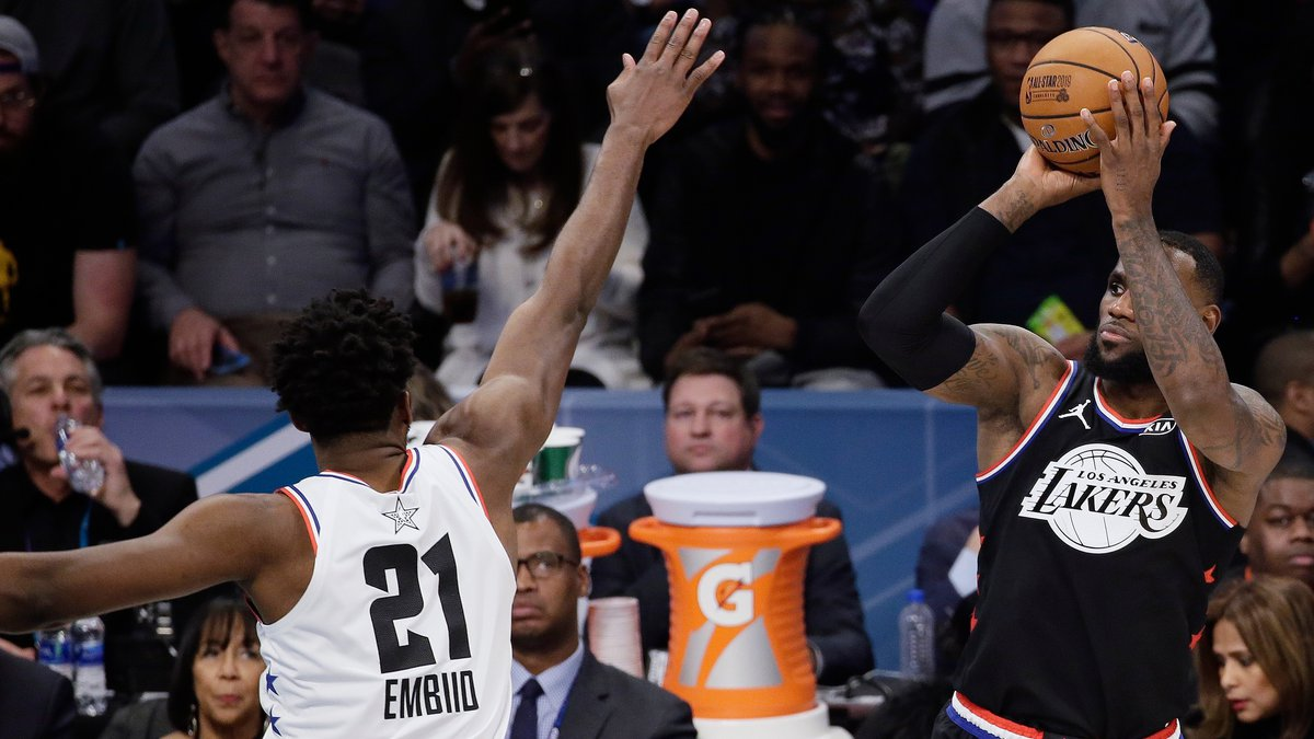 Team LeBron's LeBron James, of the Cleveland Cavaliers, shoots over Team Giannis' Joel Embiid,...