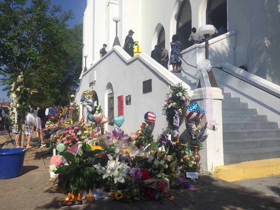 Attendees filed past a makeshift memorial of flowers and messages to the victims of Wednesday's...