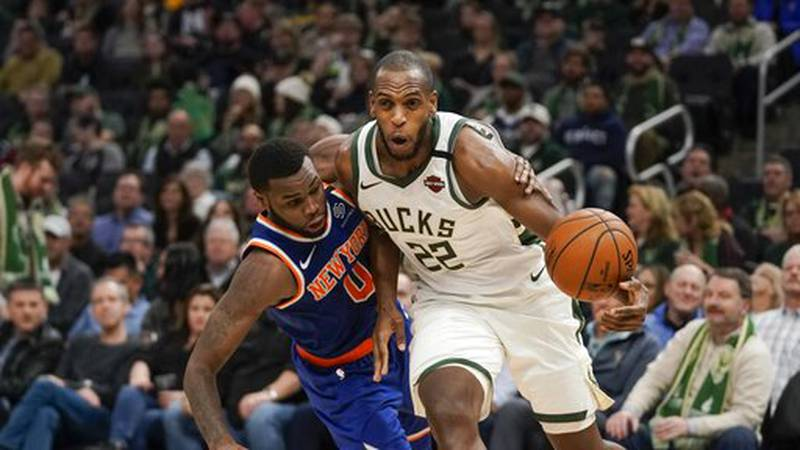 Milwaukee Bucks' Khris Middleton is fouled by New York Knicks' Kadeem Allen during the second...