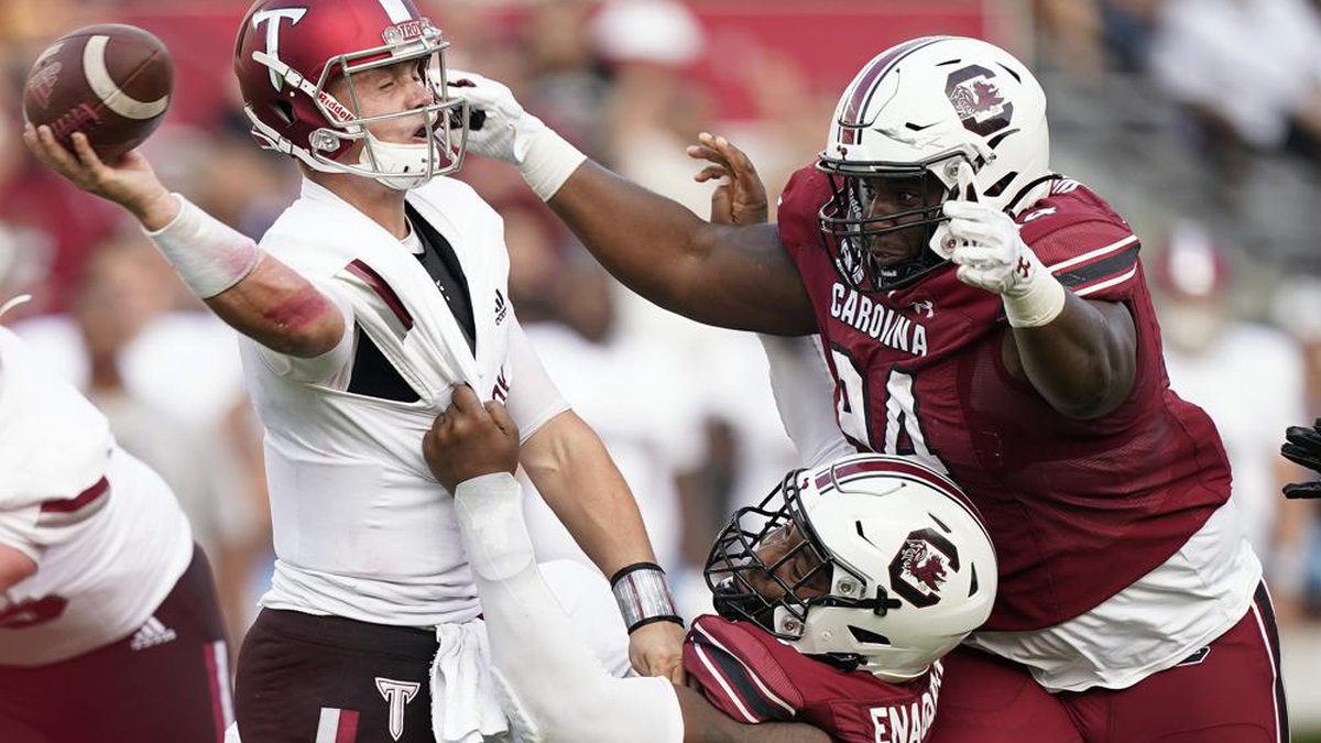 Troy quarterback Taylor Powell, left, is tackled by South Carolina defensive end Kingsley...
