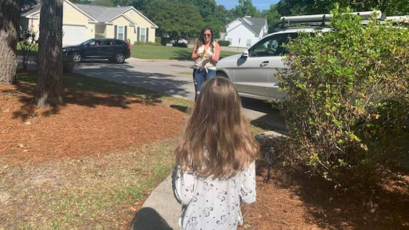 Westview Elementary 3rd grade teacher Julia Rowland delivers a book to a student Friday.