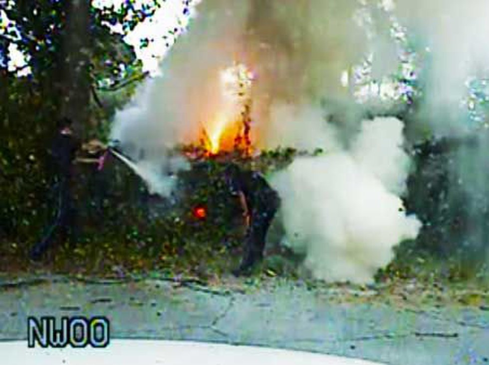 Dash cam video of police officers putting out a car fire on Monday.