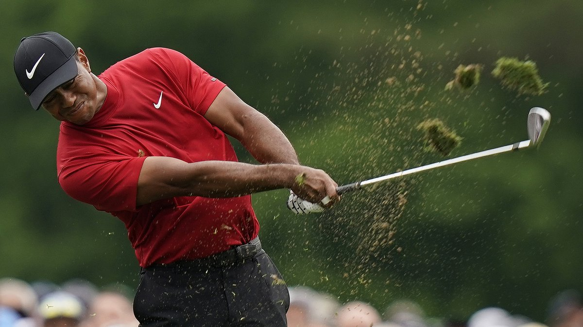 Tiger Woods hits on the 12th hole during the final round for the Masters golf tournament,...