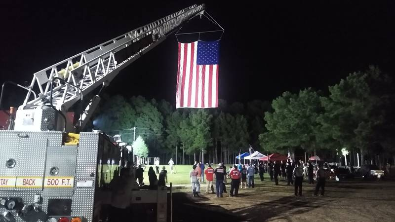 A fire truck raised a massive American flag off Pearl Street, as people came to honor the...