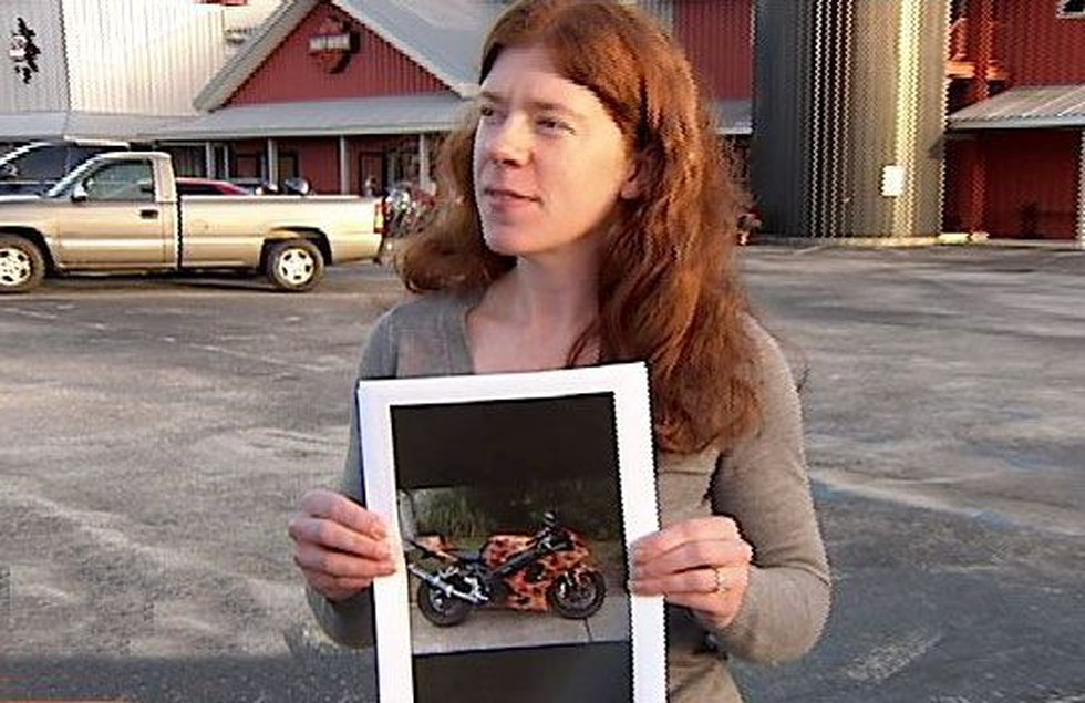 Cathleen Walker-Salazar holds up a photo of the motorcycle stolen from her husband.