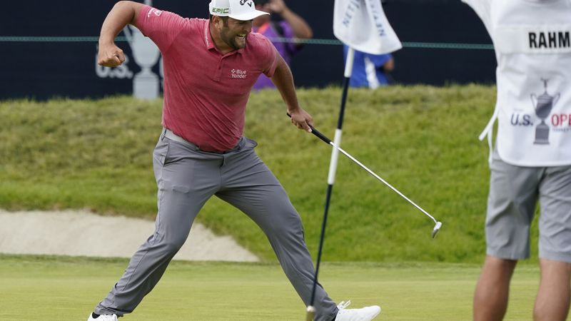 Jon Rahm, of Spain, pumps his fist after making his birdie putt on the 18th green during the...