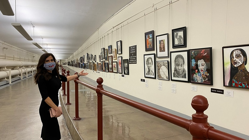 Representative Nancy Mace stands by artwork from past winners of the Artistic Discovery Contest.