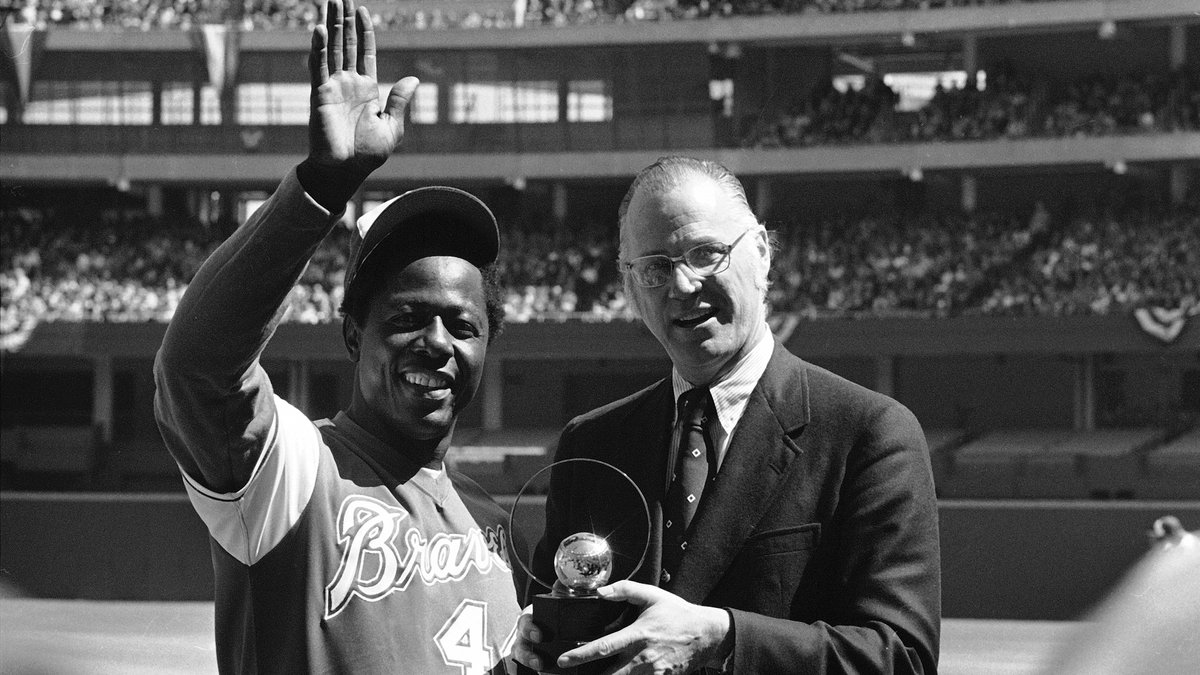 Atlanta Braves' Hank Aaron  waves to the crowd as baseball commissioner Bowie Kuhn presents him...