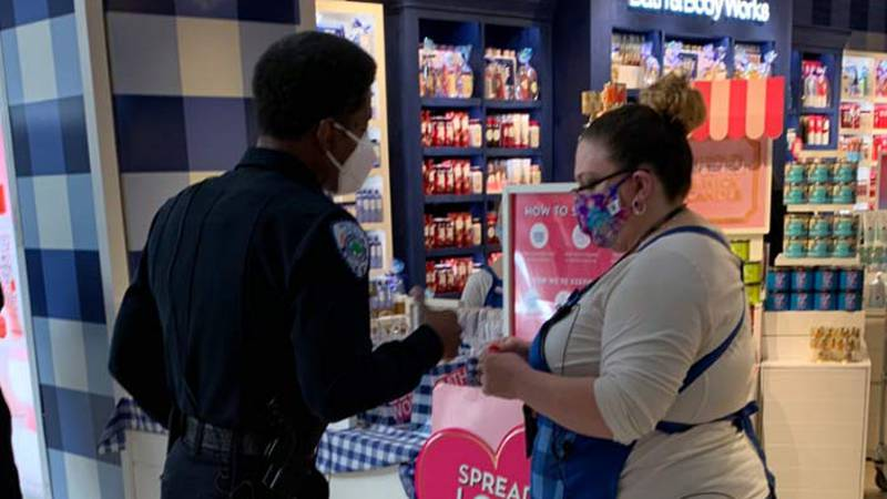 North Charleston Police Chief Reggie Burgess talks to an employee outside Bath and Body Works...