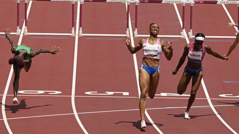 Jasmine Camacho-Quinn, of Puerto Rico, center, celebrates after winning the gold in the women's...
