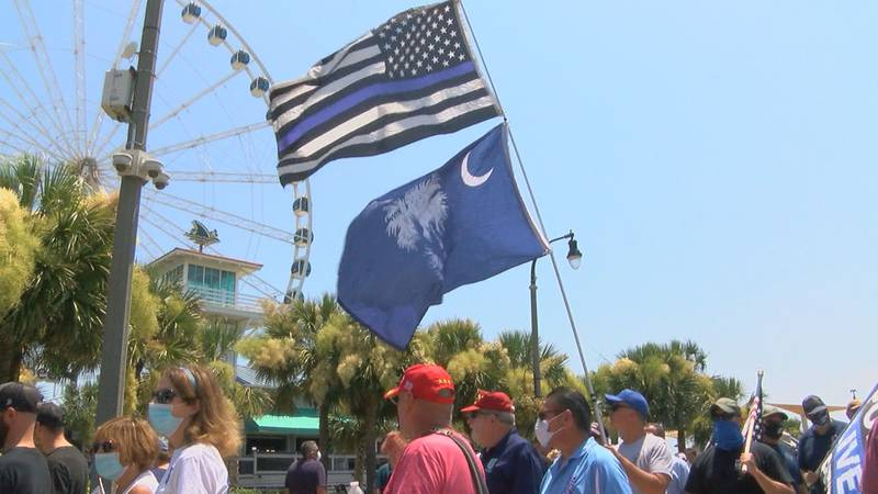 """People hoist flags and wear shirts and masks to show support for police during the """"Back the..."""