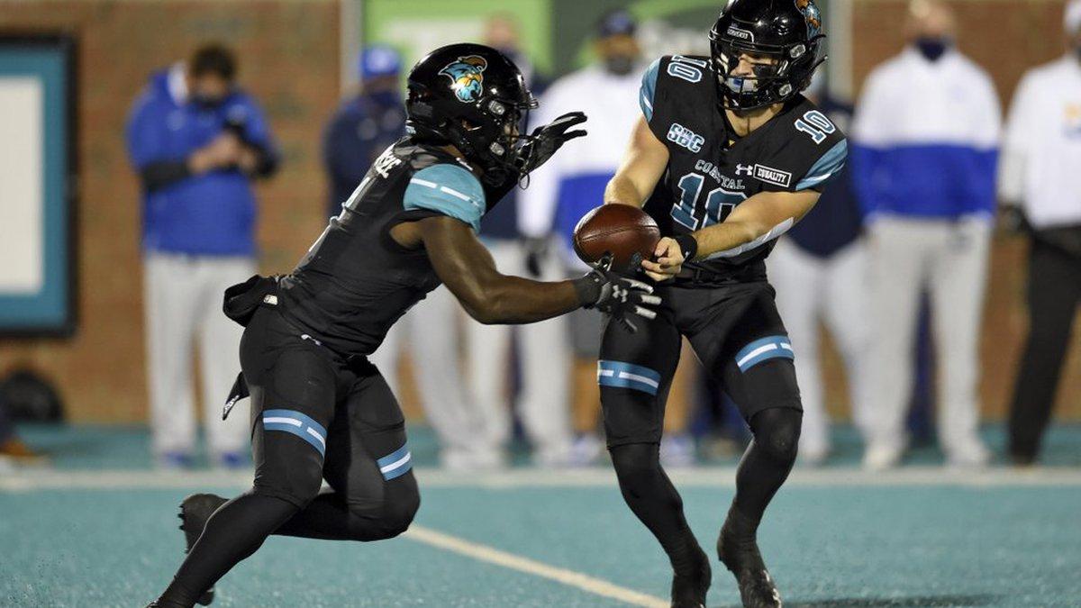 Coastal Carolina quarterback Grayson McCall, right, hands the ball off to CJ Marable during the...