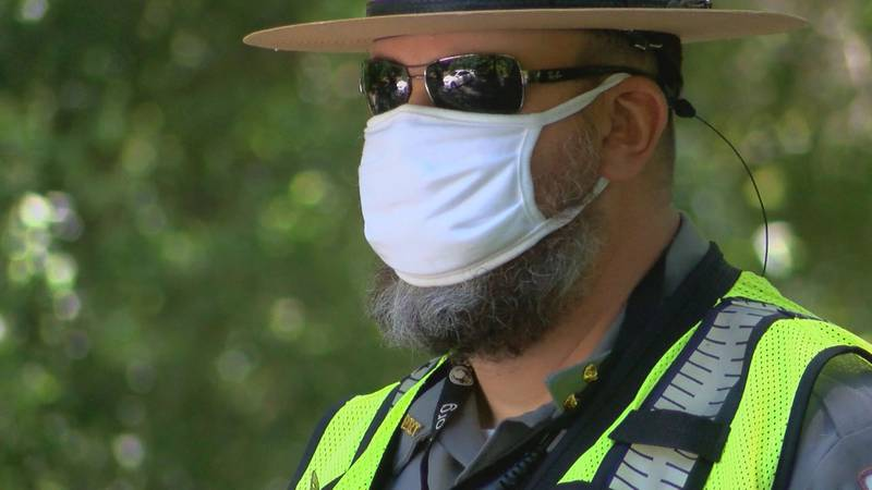 A ranger at the Myrtle Beach State Park wears a mask while turning away cars once the park hit...